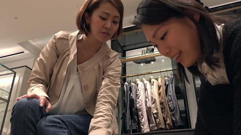 Woman Trying Shoes Talking To Asian Sales Manager In Shop Footage