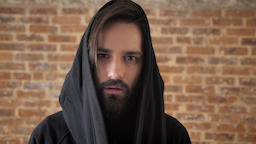 Young interesting man with beard in hood is watching at camera, goes away, brick Footage