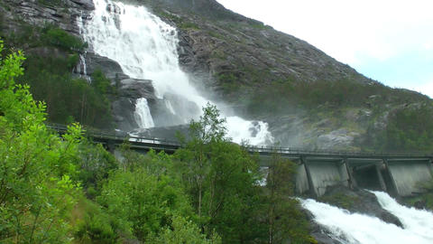 Road in Norway passing over the waterfall Langfoss. National tourist route Live Action