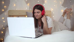 Beautiful sexy girl listening to music on headphones using laptop with good mood Footage