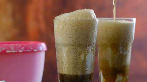 Preparing black cow cola ice cream soda floats against rustic wood background Footage
