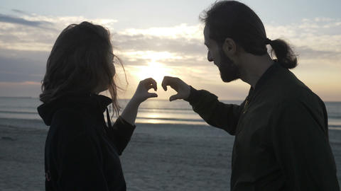 Attractive young couple sitting on the beach watching the sunset and making a Footage