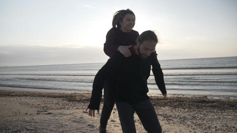 Young happy just married couple having fun on the beach playing piggy back Footage