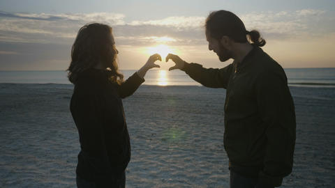 Beautiful couple making heart shape with their hands on the beach at sunrise and Footage