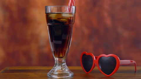 Pouring cola soft drink on ice in tall cafe glasses against a rustic wood Footage