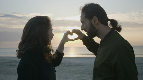Modern couple enjoying sunset at the beach and making a heart shape with their Footage