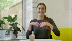 Young charming woman with ponytail sitting in cafe and looking in camera Footage
