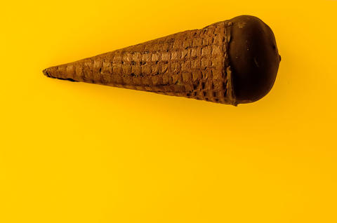 Vanilla ice cream with cranberry jam in a sugar cone dipped in chocolate Photo