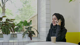 Young pretty muslim woman in hijab talking on phone and smiling, sitting in cafe Footage