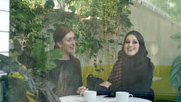 Two young womans sitting in cafe, one of them muslim woman in hijab, talking and Footage