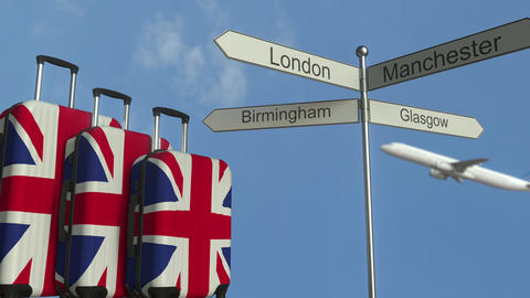 Travel baggage featuring flag of Great Britain, airplane and city sign post Live Action