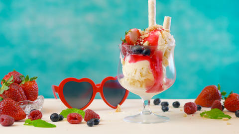 Making summertime gourmet berry and vanilla ice cream sundae Live Action