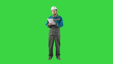 Engineer Man Verify and Read Files Documents on a Green Screen, Chroma Key Live Action