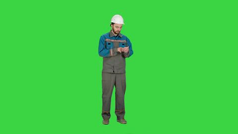 Construction worker using cell phone to send message on a Green Screen, Chroma Footage