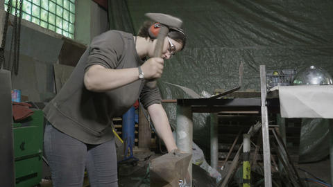 Woman blacksmith wearing protection headphones and hammering a metal bar to Footage