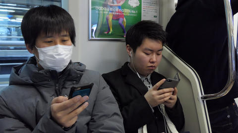 Young Japanese Men Using Smartphone While Traveling On Tokyo Train GIF