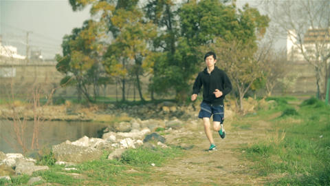 Fit young Japanese runner runs along the water at park in Japan Footage