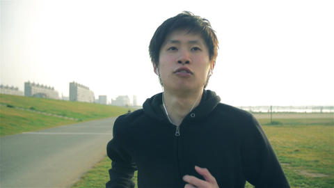 Inspirational Japanese runner man runs toward camera steadycam shot Footage