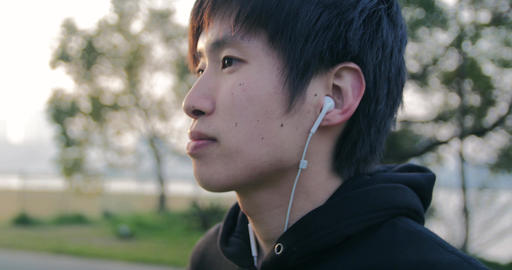 Inspiring young Japanese runner puts in earphones and gets ready to run 4K Live Action