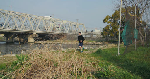 Japanese man running and training at the park near water and training tracks 4K Footage