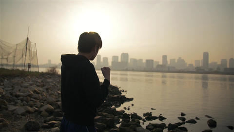 Young Japanese man shadow boxing at dawn down at the river in Japan Footage