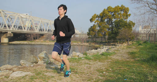 Young Japanese running training along the water in Osaka 4K Footage