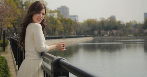 Attractive Japanese girl wearing white dress watching the cherry bloosoms at par Footage