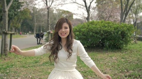 Beautiful Japanese girl sitting on grass throwing leaves in the air Slow motion- Footage