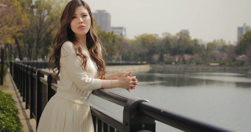 Beautiful Japanese young women leans agaisnt railing at the park smiles at the c Footage