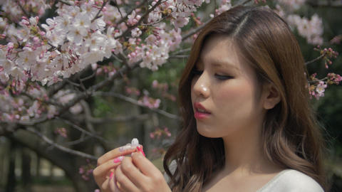 Beautiful young Japanese women plays with flowers and her hair Slow motion- Footage