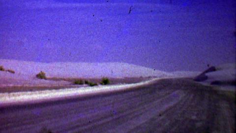 1957: Winter Snow Drift Blows Across Barren Road Landscape stock footage