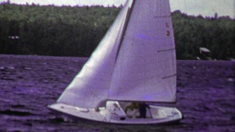 1961: Sailboat full speed ahead on choppy dark blue waters Footage