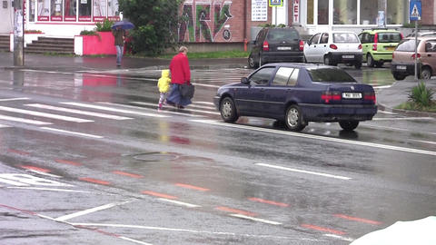Grandmother with grandson crossing on a pedestrian crossing a street with many c Footage