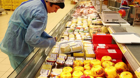 Saleswoman arranges cheese on a showcase in a large supermarket Live Action