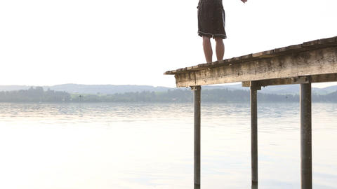 Young man jumps off the dock into water Footage