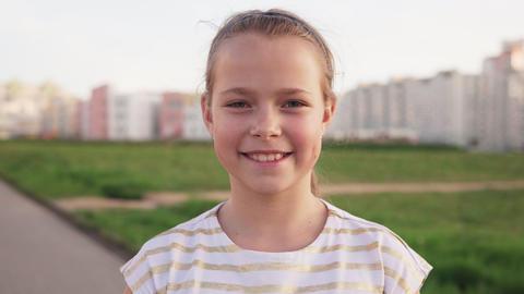 Little joyful girl smiling against urban lawn Footage