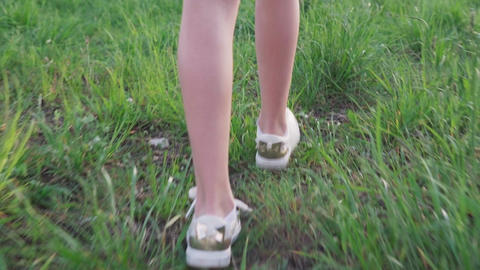 Legs little girl walking on grass Live Action