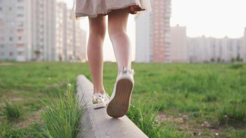 Legs of little girl walking on concrete log on urban lawn Footage