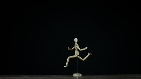 Stopmotion running wooden figure dummy in studio on black background rotates Live Action
