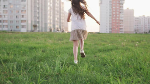 Little girl running on grass on urban wasteland Live Action