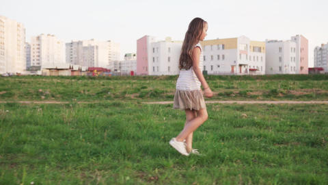 Cute little girl walking on grass on urban wasteland Live Action