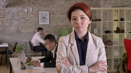 Young business asian woman with crossed hands looking in camera in modern office Footage