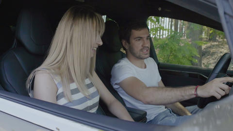 Young man with young girl using sensory dashboard inside the modern auto Footage