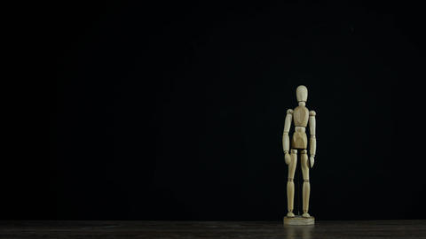 Stopmotion wooden figure dummy in studio on black background salutes and marches Live Action