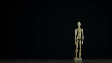 Stopmotion wooden figure dummy in studio on black background stands and rotates Live Action