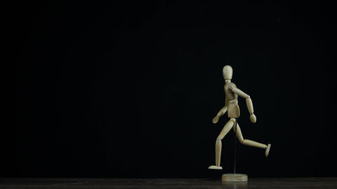 Stopmotion running wooden figure dummy rotates in studio on black background for Live Action