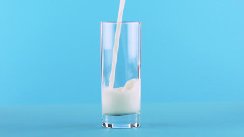 Slow motion close-up shot of milk cold beverage drink pooring into glass blue Live Action