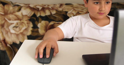 Child work with PC mouse near the laptop on white table Live Action