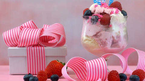 Pink Ice Cream Sundae with birthday candles and gift on a summery feminine pink Footage