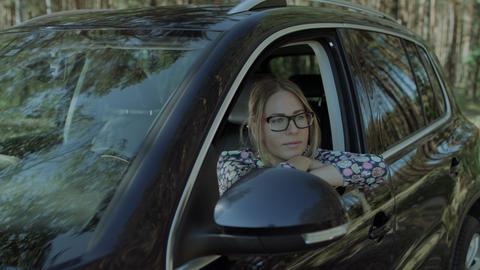 Beautiful woman leaning on car door on road trip Footage